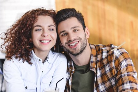 Photo for Beautiful man and woman smiling and looking away at cafe - Royalty Free Image