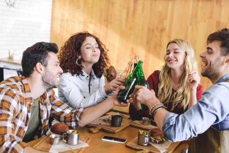 Photo for Handsome and attractive friends smiling and cheering with glass bottles at cafe - Royalty Free Image
