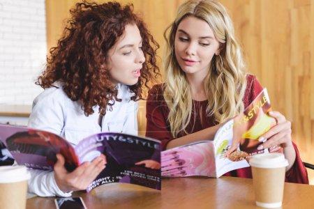 Photo pour Belles femmes souriantes lisant des magazines et parlant au café - image libre de droit