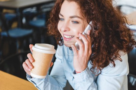 Photo for Attractive and smiling woman holding paper cup and talking on smartphone - Royalty Free Image