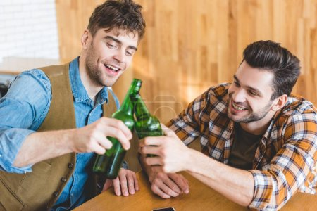 Photo for Handsome and smiling men cheering with glass bottles of beer - Royalty Free Image