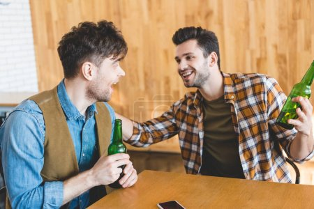 Photo for Handsome and smiling men holding glass bottles of beer and talking - Royalty Free Image