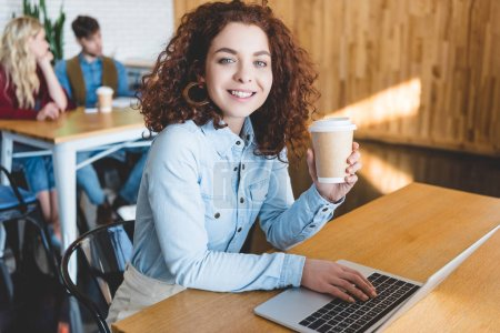 Photo for Selective focus of attractive  woman holding paper cup and using laptop at cafe - Royalty Free Image
