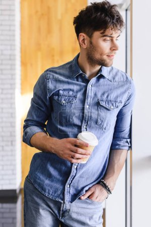 Photo for Handsome man standing and holding paper cup at cafe - Royalty Free Image