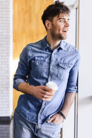handsome and smiling man standing and holding paper cup at cafe