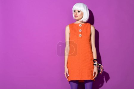Pretty girl in wig and orange dress looking away on purple background