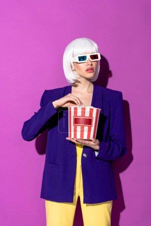Elegante chica en peluca y gafas 3d comiendo palomitas de maíz sobre fondo púrpura