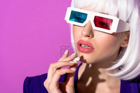 Fille rêveuse dans des lunettes 3D manger du pop-corn isolé sur violet
