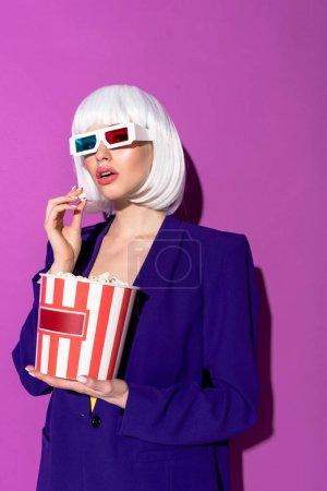 Photo pour Élégante jeune femme à lunettes 3d manger maïs éclaté sur fond violet - image libre de droit