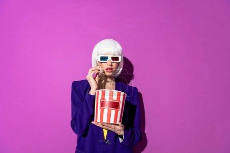 Photo pour Femme stupéfaite en perruque et des lunettes 3d manger maïs éclaté sur fond violet - image libre de droit