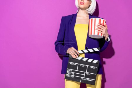 Photo for Cropped view of woman in blue jacket holding popcorn and clapperboard on purple background - Royalty Free Image