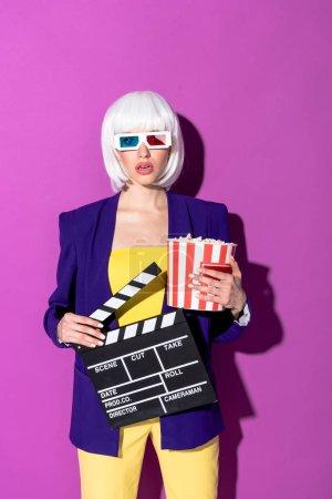 Photo pour Fille étonnée dans lunettes 3d tenant le pop-corn et clap sur fond violet - image libre de droit