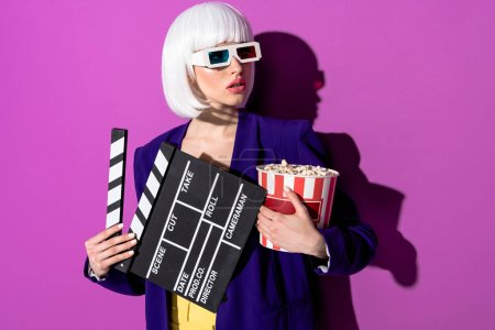 Photo for Worried girl in 3d glasses holding clapperboard and popcorn on purple background - Royalty Free Image