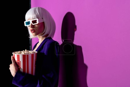 Interested girl in 3d glasses holding popcorn on purple background