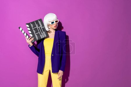 Photo for Elegant woman in 3d glasses holding clapperboard and looking away on purple background - Royalty Free Image