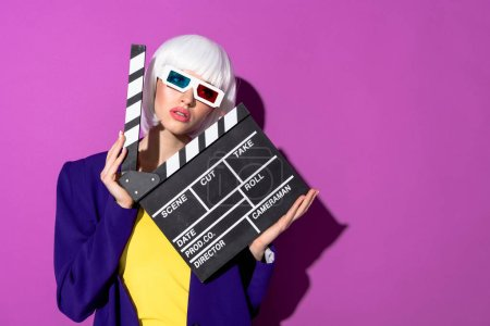 Photo for Girl in white wig and 3d glasses holding clapperboard on purple background - Royalty Free Image