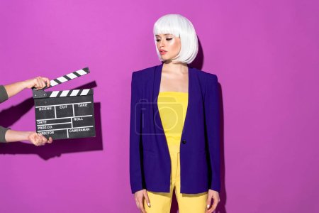 Photo for Sensual girl in white wig looking at clapperboard on purple background - Royalty Free Image