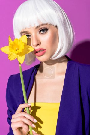 Stylish girl in white wig holding flower and looking at camera on purple background