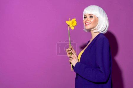 Photo pour Fille inspirée en perruque blanche tenant fleur et souriant sur fond violet - image libre de droit
