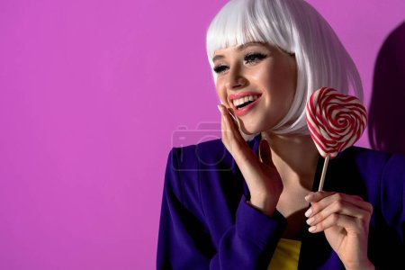 Photo for Laughing girl in white wig holding lollipop on purple background - Royalty Free Image