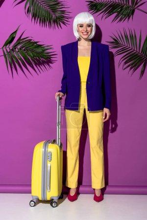 Photo pour Vue pleine longueur de fille souriante en perruque avec valise jaune debout sur fond violet - image libre de droit