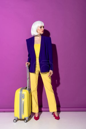 Photo pour Femme élégante en perruque avec valise jaune regardant loin sur fond violet - image libre de droit