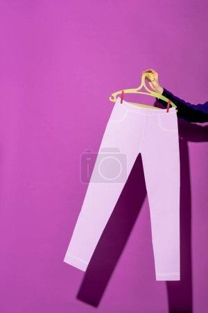 Photo for Cropped view of woman holding hanger with paper pants on purple background - Royalty Free Image