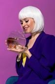 """Постер, картина, фотообои """"Улыбающаяся девушка в белых Холдинг аквариум с Золотые рыбки, изолированные на фиолетовый парик"""""""