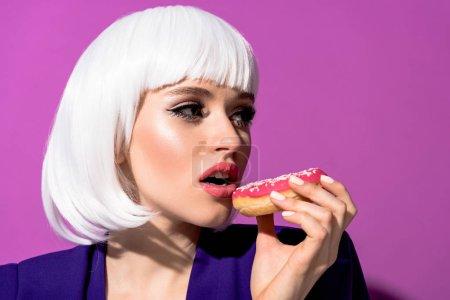 Photo pour Jolie fille en perruque blanche manger en anneau sur fond violet - image libre de droit