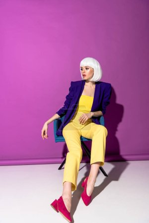 Photo for Elegant girl in white wig sitting in armchair and looking away on purple background - Royalty Free Image