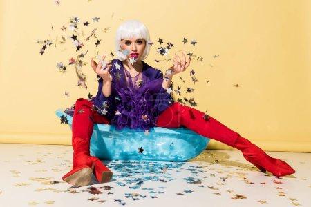 Photo pour Fille sérieuse en perruque assis dans la baignoire bleu et jeter des confettis étoiles sur fond jaune - image libre de droit