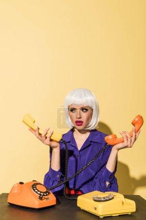 Photo pour Femme confus en perruque blanche tenant des combinés sur fond jaune - image libre de droit