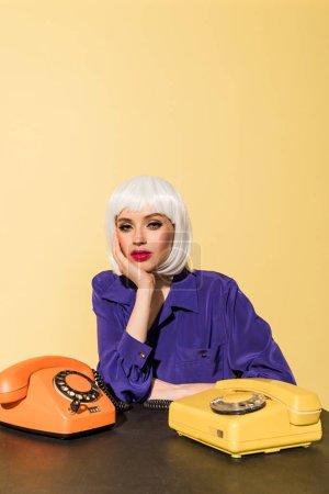 Photo pour Femme curieuse en perruque posant avec de vieux téléphones isolés sur jaune - image libre de droit