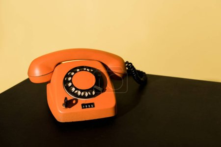 Photo for Old orange telephone standing on black surface on yellow background - Royalty Free Image