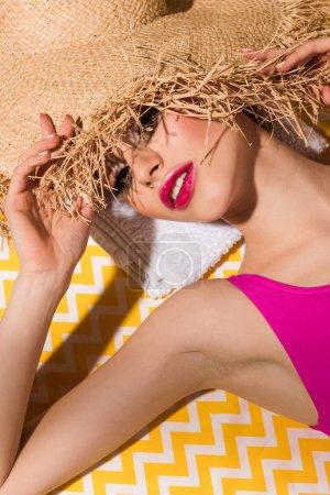 Foto de Mujer joven atractiva en sombrero de paja sobre la superficie amarilla - Imagen libre de derechos