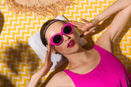 Photo for Woman in sunglasses and swimsuit lying on towel on yellow background - Royalty Free Image