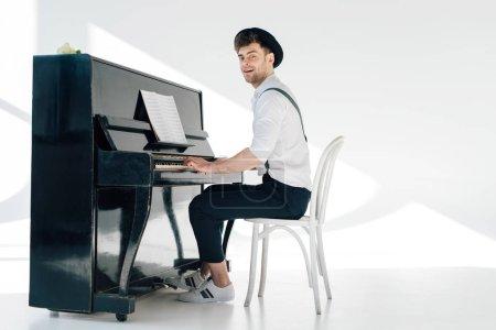Photo pour Pianiste souriante en vêtements à la mode au piano - image libre de droit