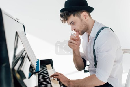 Photo for Thoughtful musician composing music while sitting at piano - Royalty Free Image