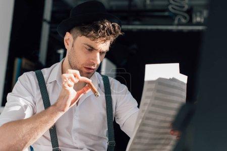 Photo pour Mise au point sélective du musicien beau cigare, lecture de notes sur la musique des feuilles de livre - image libre de droit