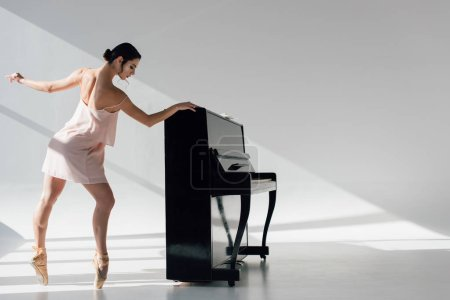 Photo pour Belle jeune ballerine dansant au soleil près du piano noir - image libre de droit