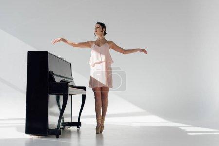 Photo pour Jeune belle ballerine dansant près de piano noir - image libre de droit