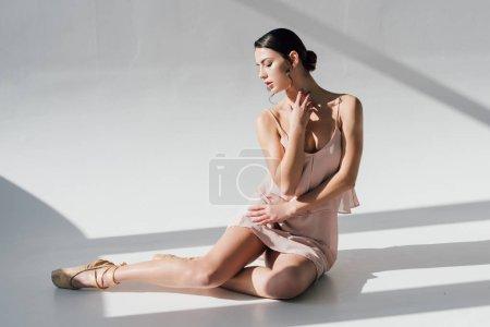 Photo pour Jeune ballerine en robe rose assise au soleil - image libre de droit