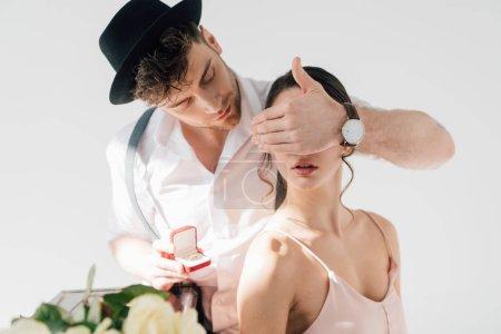 Photo pour Bel homme faisant la demande en mariage à la belle fille, tout en fermant les yeux avec la main - image libre de droit