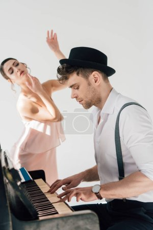 Photo for Selective focus of handsome pianist playing piano while young ballerina dancing near him - Royalty Free Image