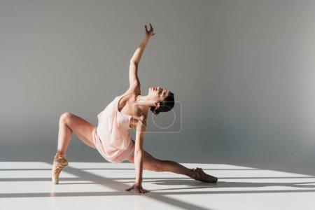 Photo pour Gracieuse jeune ballerine en robe rose dansant au soleil - image libre de droit