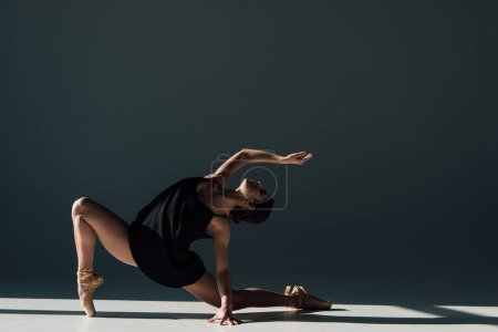 Photo pour Gracieuse jeune ballerine en robe noire dansant au soleil - image libre de droit