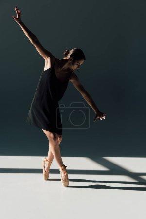 Photo pour Belle jeune ballerine dansant en robe noire et pointes chaussures - image libre de droit