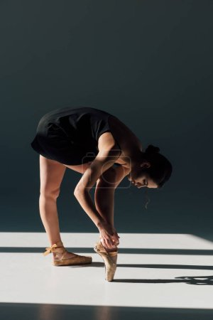 Photo for Young ballerina in black dress fixing pointe shoes - Royalty Free Image