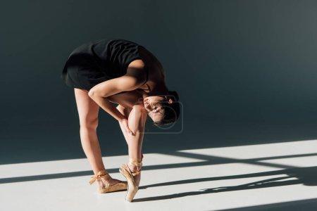 Photo pour Jeune ballerine en robe noire étirant à la lumière du soleil - image libre de droit