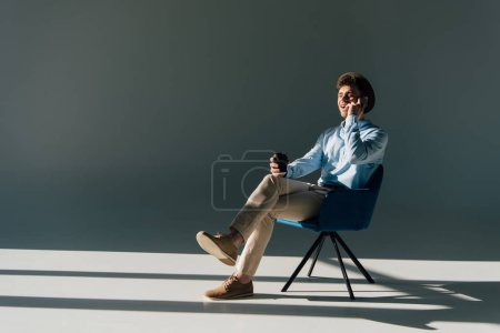 smiling man talking on smartphone while sitting on chair in sunlight